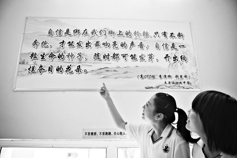 """快看,我们俩写的自信标语展示在了学校的走廊里。   自信是绑在我们脚上的铃铛,只有不断奔跑,才能发出最响亮的声音6月24日下午,太原市29中的教学楼里,十多名高三毕业班的学生返回母校,将悬挂在楼道里的名言警句标牌一一擦拭,合影留念。墙上的名言警句是学校文化长廊的一部分,出自学生之手。文化长廊是太原市29中的创意教学方式之一,也是同学们心中难忘的风景线。   在应试教育盛行的今天,我们需要拿出实际行动来证明素质教育的意义:成人和成才、成功一样重要。""""文化长廊""""只张贴学生们自己的作品,它的"""